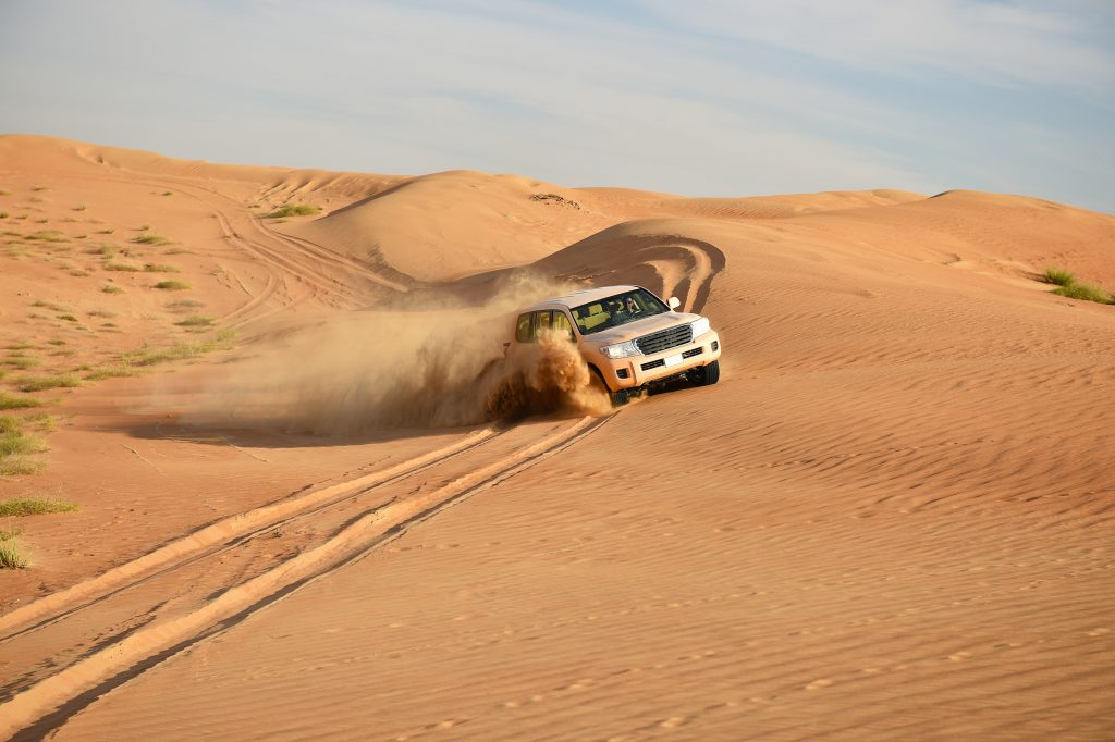 4X4 car driving in desert sand dunes