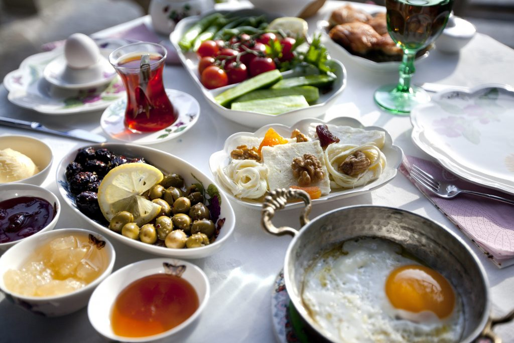 turkish breakfast with sunny side up eggs, olives, jam and fruits