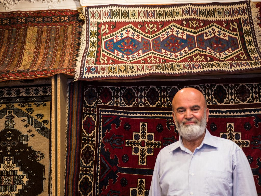 Elderly Turkish man smiling inside a rug shop in cappadocia