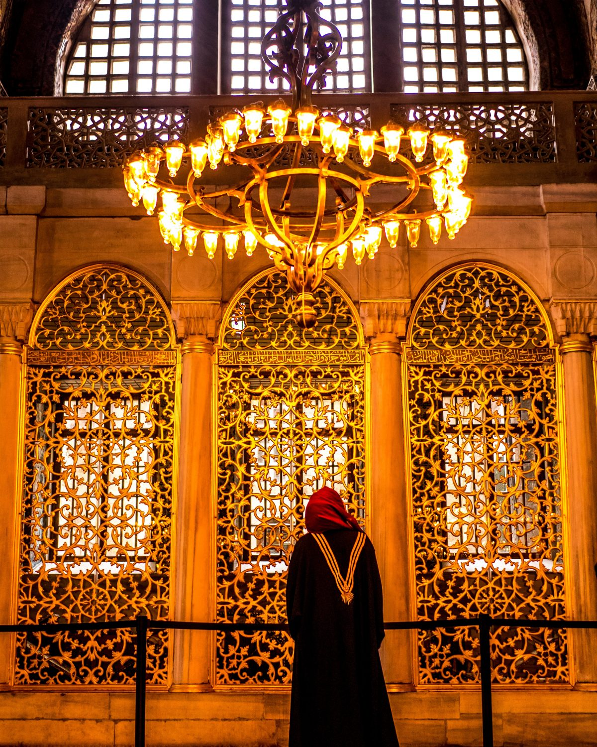 A lady in hijab standing inside the Hagia Sopphia, by a golden lattice barrier that separates the library from the public