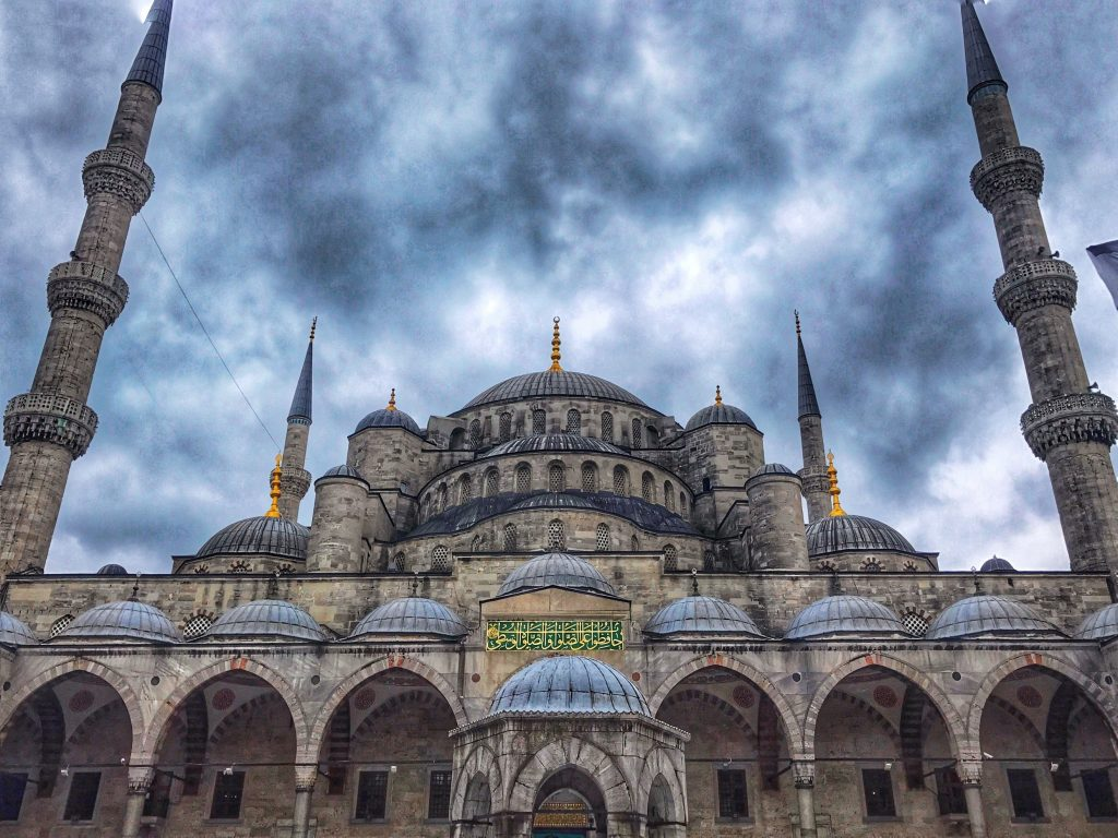 The blue mosque in sultanahmet istanbul. Two minarets and many domes set against a stormy blue sky