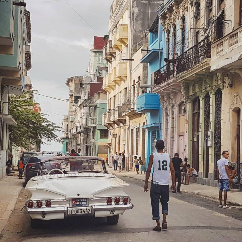 Man walks past a vintage car in Havana, Cuba