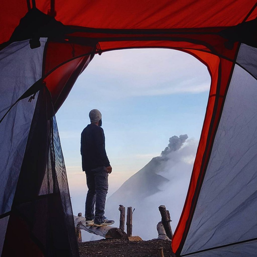 man stands by the entrance of a tent on acatenango volcano