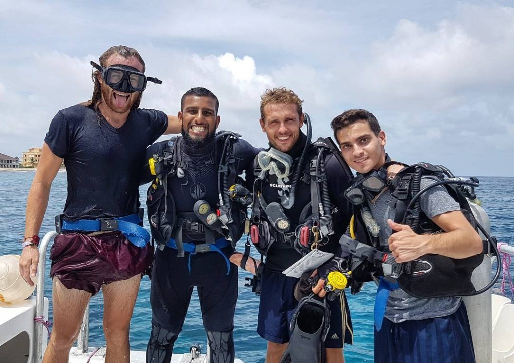 4 men about to scuba dive in the sea in Honduras