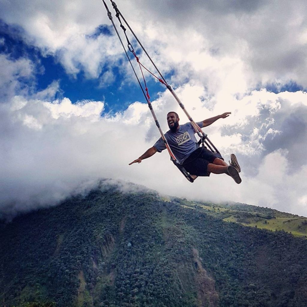 British Asian swinging on wooden seat over a mountain in Latin America
