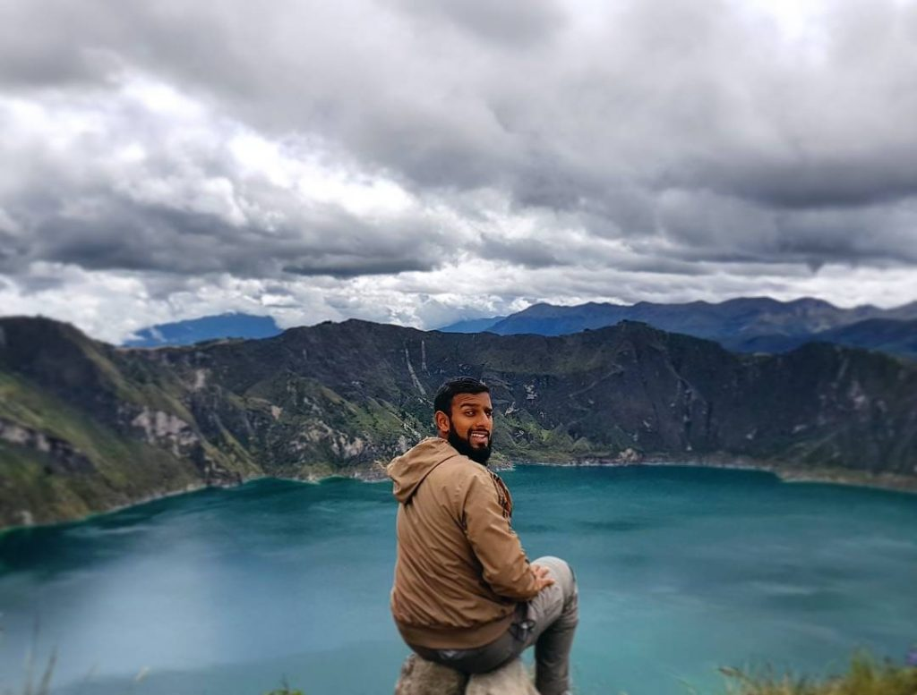 Asian man Sitting on the rim of Quilotoa, a volcano in the Andes