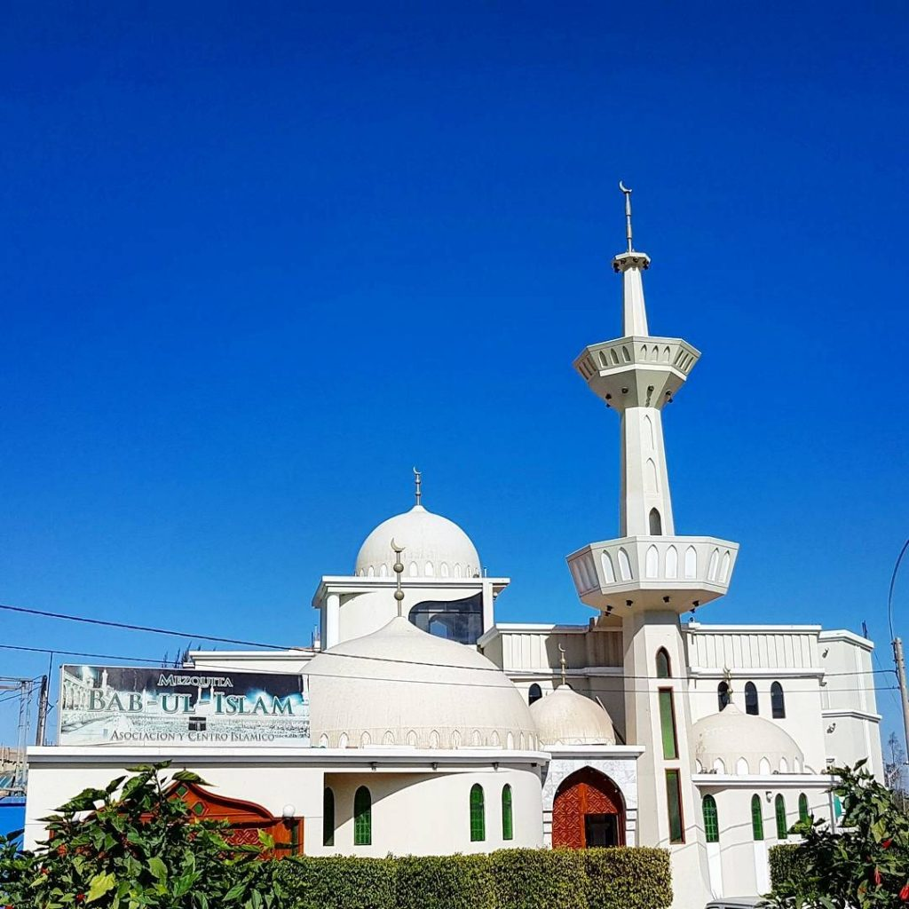 white mosque with 2 domes and a minaret