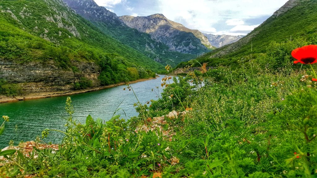 the jade green neretva passes through a valley surrounded by green mountains in bosnia