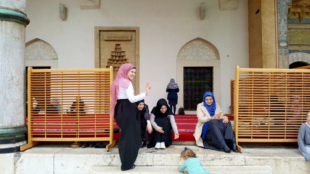 Muslim women wearing pink, blue and black cooured headscarfs sit outside a mosque