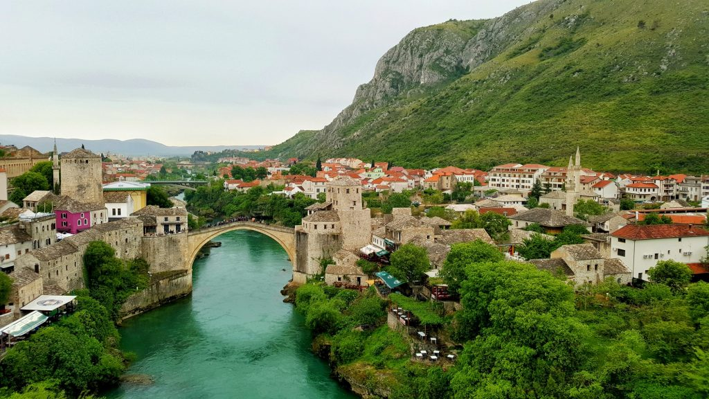view of the jade green neretva river passing underneath the Old Bridge in Mostar, Bosnia