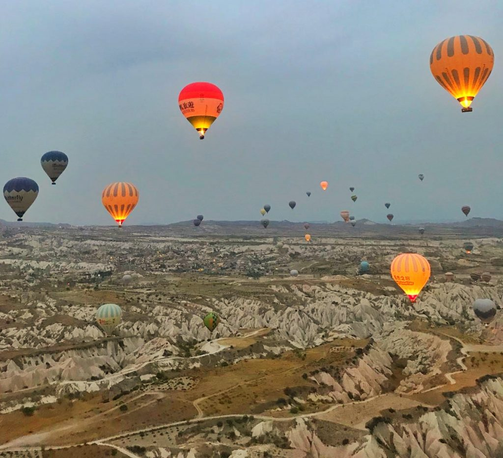 multicoloured hot air balloons fly over rocky landscape in cappadoia