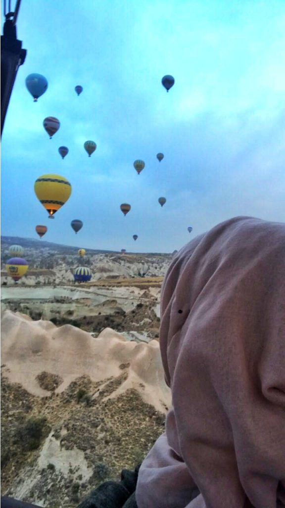 lady in a headscarf looking at the hot air balloons floating in the sky