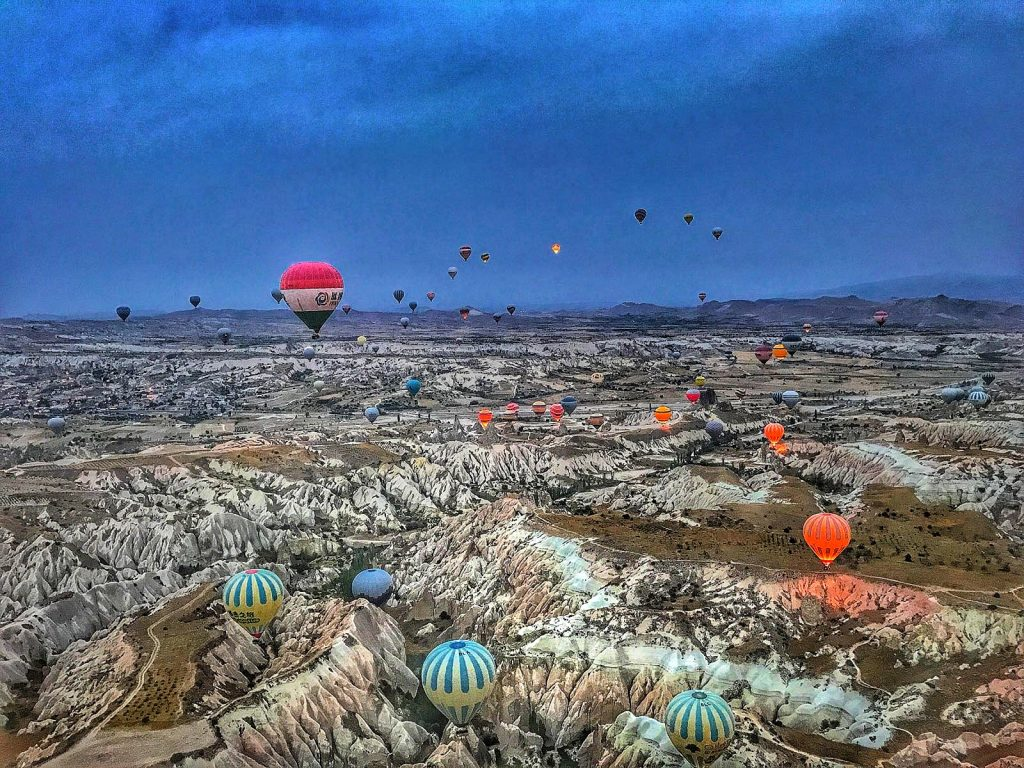multicoloured hot air balloons fly over rocky terrain in cappadocia