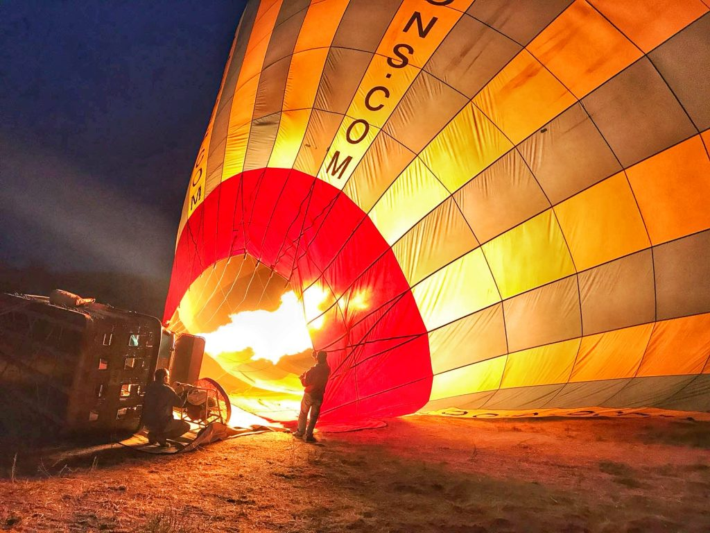 yellow and blue hot air balloon lying horizontally on the ground. Fire is blown into the balloon and a man stands nearby to supervise.