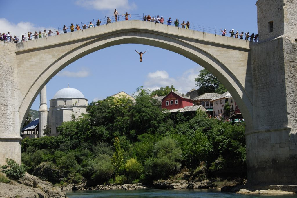 A man dives off the old bridge in mostar. in the background is the koski mehmet pasha mosque