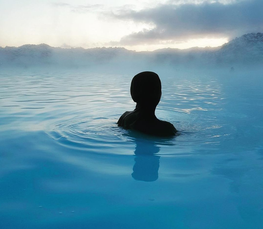 Muslim woman in a burkini swims in the blue lagoon in iceland