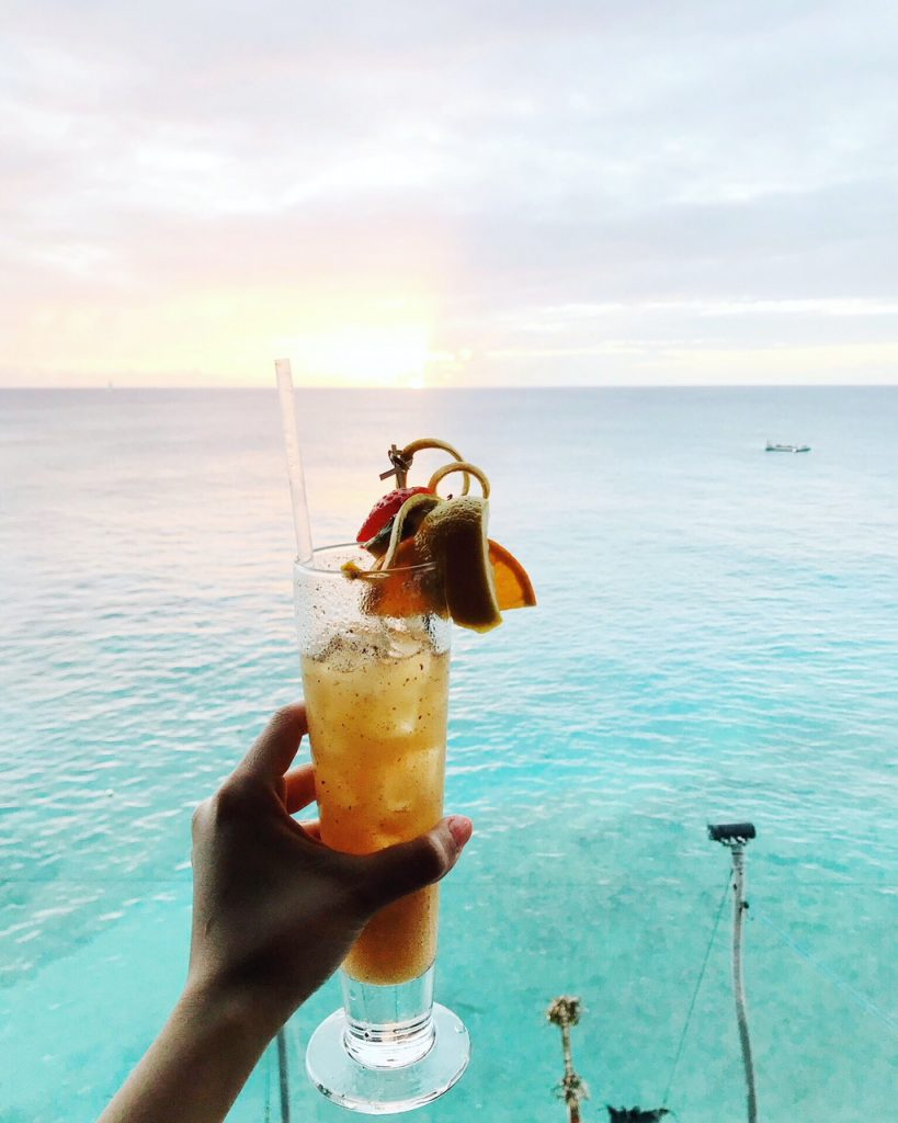 drinking a mockail with a view of the caribbean in Barbados