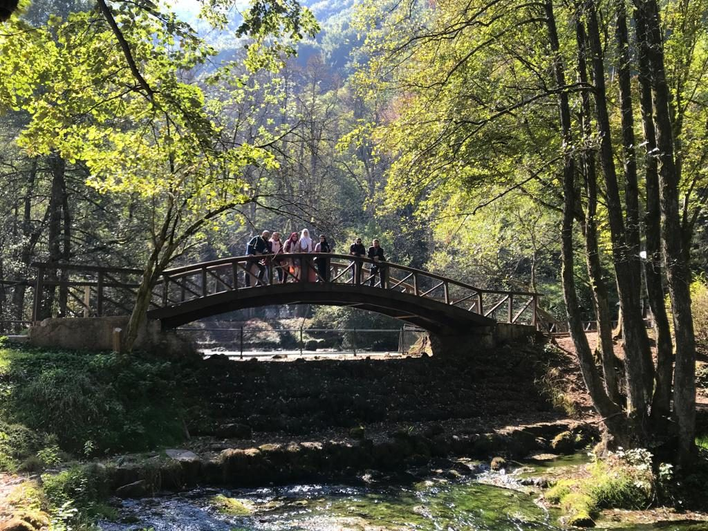 group of friends stand on a bridge in vrelo bosne, bosnia