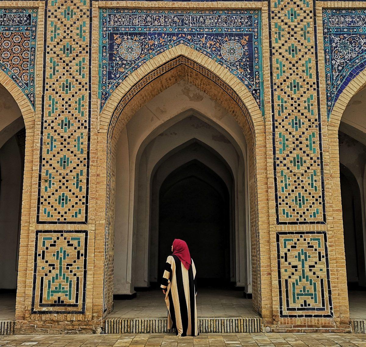 Muslim woman in red hedscarf and abaya in Uzbekistan