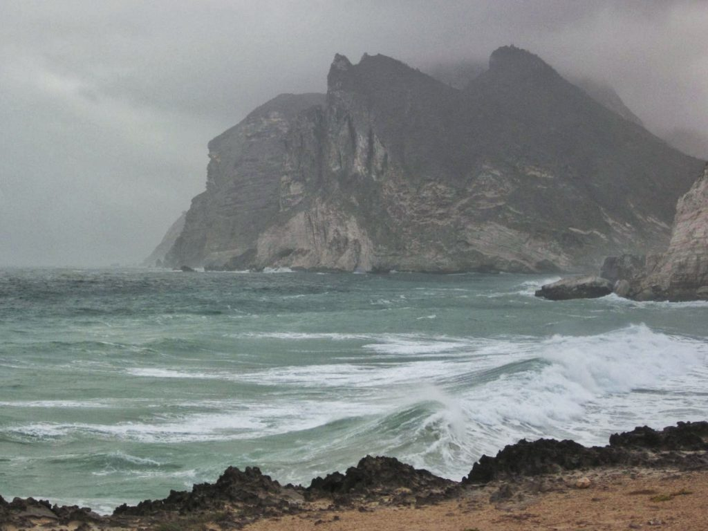 White foaming waves crash against the cliff during the Khareef season in Salalah, Oman.