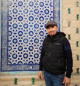 Uzbek local in front of blue tiled wall