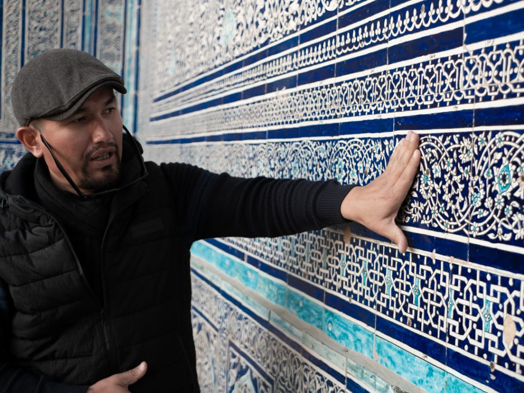 Uzbek local with hands on blue tiled wall in Khiva