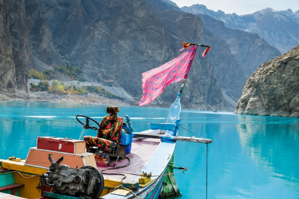 A colorful docked boat at turquoise Attabad lake with mountains in the background. Gojal Hunza valley, Gilgit Baltistan, Pakistan.