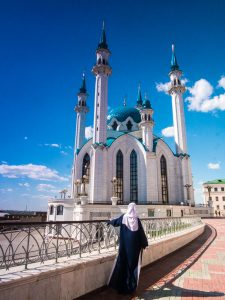 woman in hijab in front of white mosque