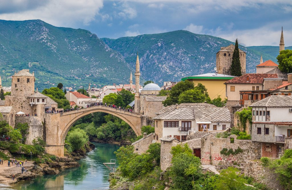 view of the green neretva river flowing under curved ottoman bridge iin mostar, bosnia ottoman legacy