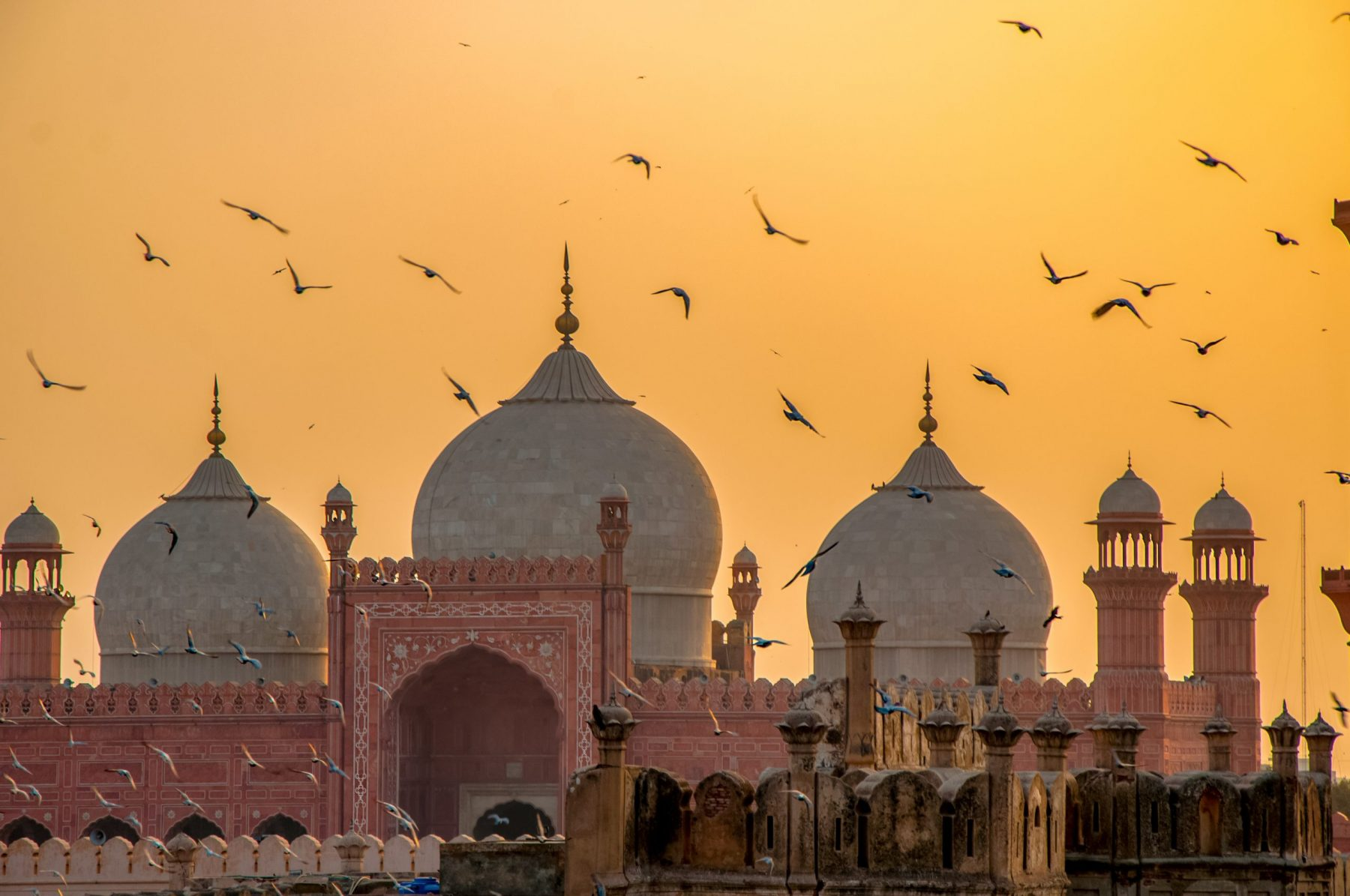red sandstone walls of badshahi mosque at sunset
