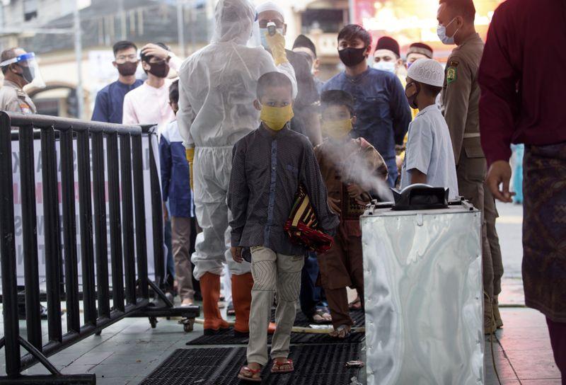 Muslim boy walks past sanitiser spray before entering mosque in indonesia