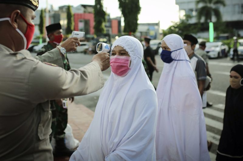 muslim women wearing face masks in indonesia mosques reopen under Covid-19 restrictions
