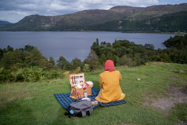 muslim woman enjoys picnic at lake derwentwater. Explore the best of the UK countryside: 6 day itinerary to North England