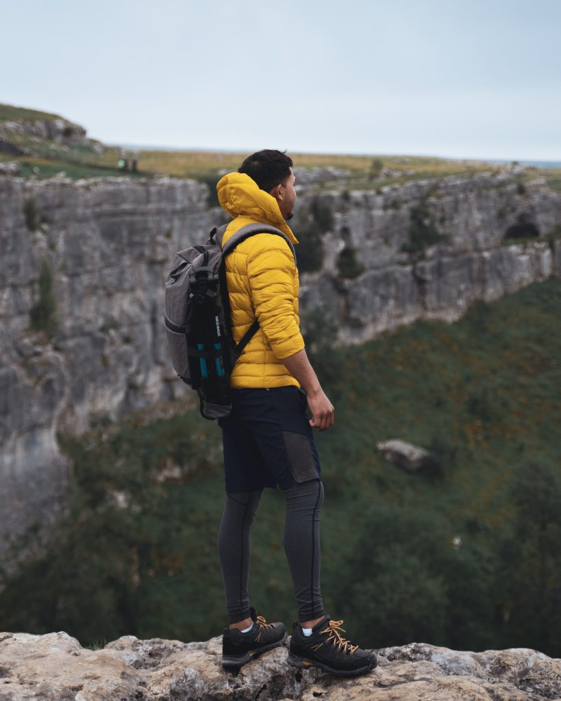 man in yellow jacket stands at malham cove england Explore the best of the UK countryside: 6 day itinerary to North England